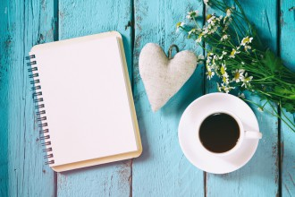 vintage filtered and toned top view image of daisy flowers, blank notebook and fabric heart next to cup of coffee on blue wooden table. vintage filtered and toned