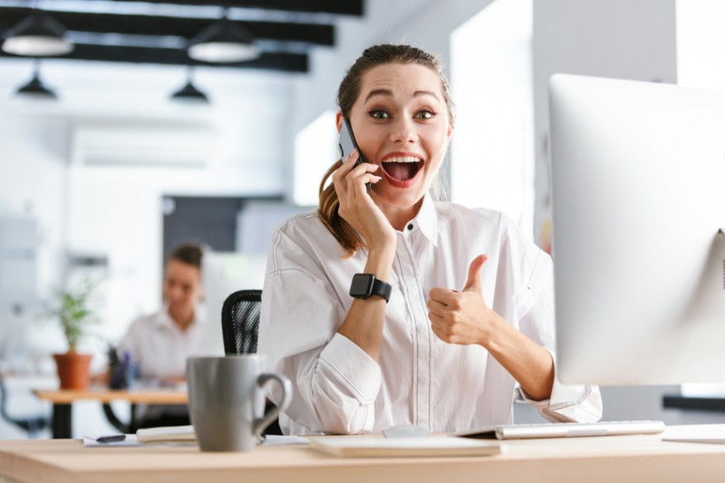 Happy young businesswoman dressed in shirt sitting at her workplace at the office, talking on mobile phone